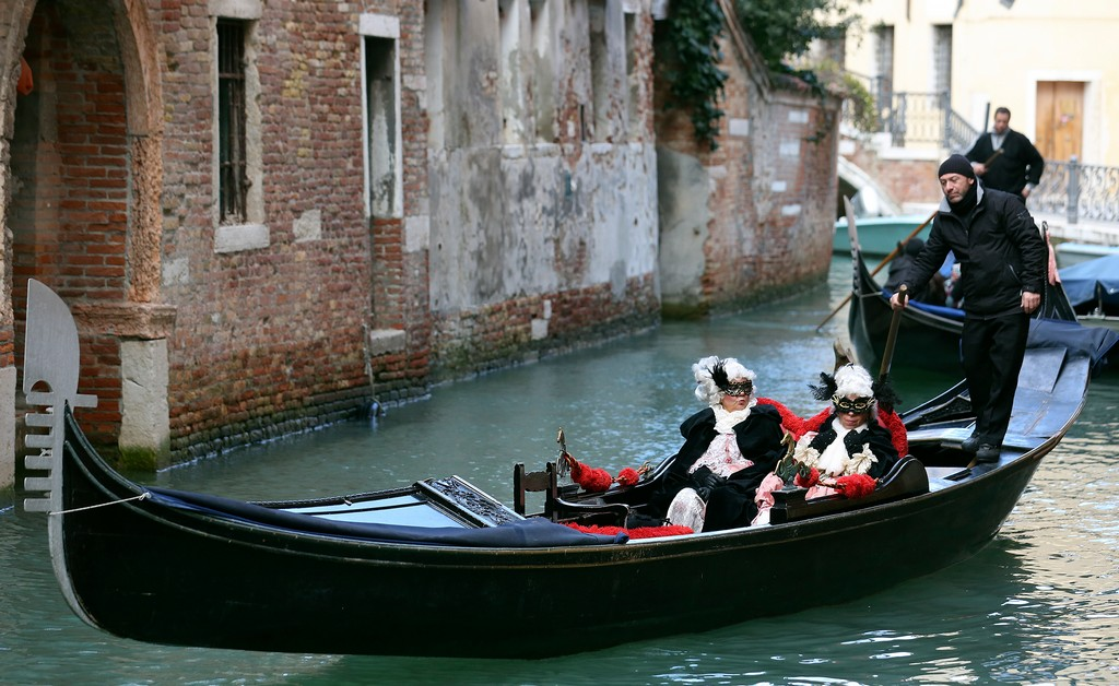 Masked revellers ride a gondola during the Venice Carnival