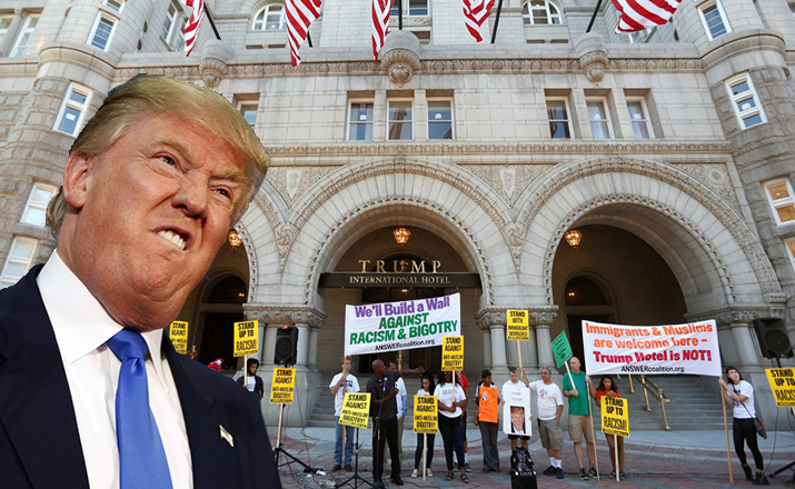 Protesters hold signs outside the new Trump International Hotel on it's opening day in Washington