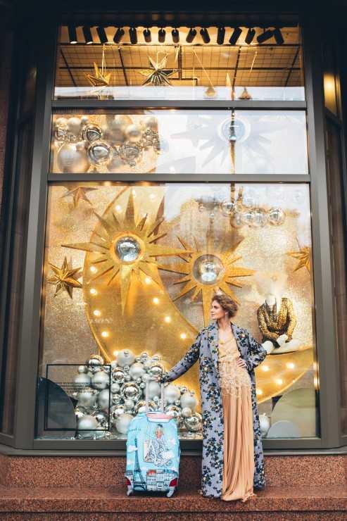 Пальто, платье: AYSINA. Украшение: серьги – Guzema Fine Jewelry. Чехол для чемодана: «Девочка на шаре» Travel is... Локация: ЦУМ (TSUM)
