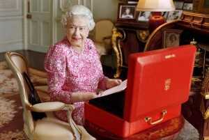 A handout photograph shows Britain's Queen Elizabeth sitting in her private audience room in Buckingham Palace next to one of her official red boxes in London