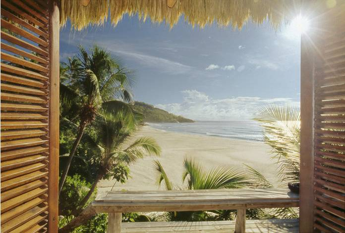Opened wooden window on wild tropical beach